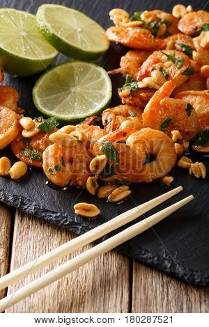 Asian Food: Sauteed Shrimp With Peanuts, Lime And Greens Closeup. Vertical