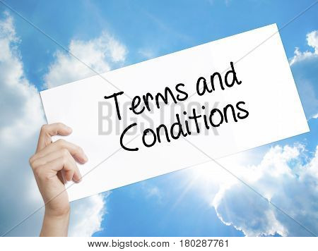 Man Hand Holding Paper With Text Terms And Conditions . Sign On White Paper. Isolated On Sky Backgro