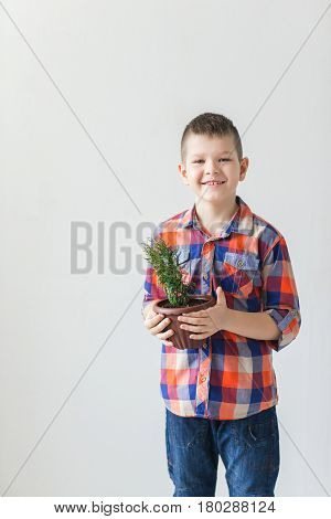 Happy child on white background with pot of plant.