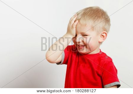 Face expressions children concept. Portrait of happy kid boy making funny silly faces with hand on forehead