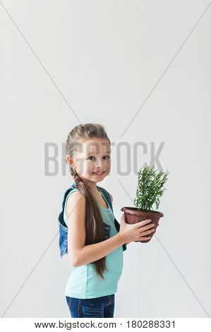 Girl standing on a white background with a plant on Earth Day.