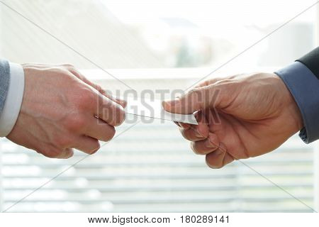 Young businesspeople exchanging Visiting Card In Office. You can use the blank visiting card as copyspace.