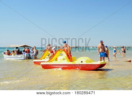 ANAPA, RUSSIA - SEPTEMBER 12, 2016: Beach vacation. Children ride from hills of catamarans to shallow waters of sandy beach. Group of vacationers goes on sea excursion in small boat under thatched canopy