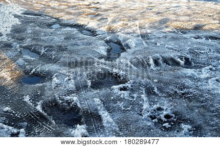Spring. Melting snow and puddles on road. Traces of car tires were imprinted on wet ice. Bright sun and shadow