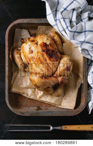 Grilled baked whole organic chicken on backing paper in old oven tray with white kitchen towel and meat fork over black burnt wooden background. Top view with space.