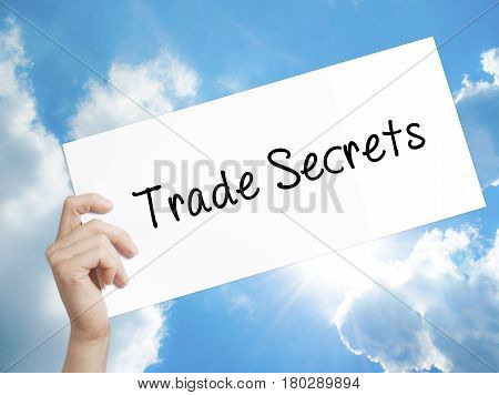 Man Hand Holding Paper With Text Trade Secrets . Sign On White Paper. Isolated On Sky Background