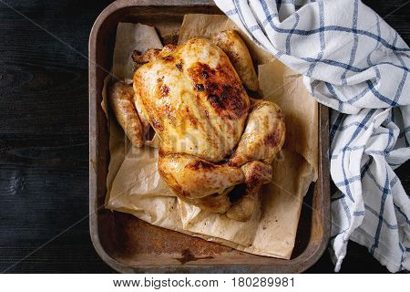 Grilled baked whole organic chicken on backing paper in old oven tray with white kitchen towel over black burnt wooden background. Top view with space.