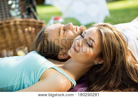 Couple in park on picnic. top view of a couple in love lying on a picnic plaid. Young loving couple think about their dreams at picnic outdoors.