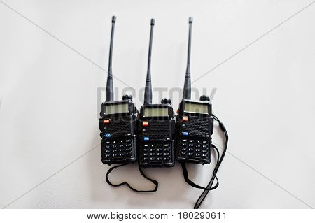 Three Portable Radio Transmitter At Steel Background.