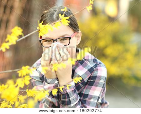 Girl is blowing her nose allergic to bloom flowers