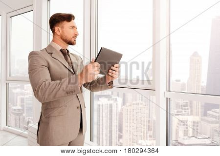 Find new prospects. Pleasant confident businessman standing near window and enjoying the view while using tablet