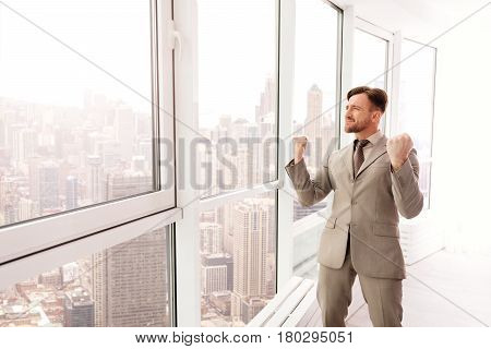 I am the winner. Positive delighted businessman standing in the office and celebrating his victory while expresssing gladness