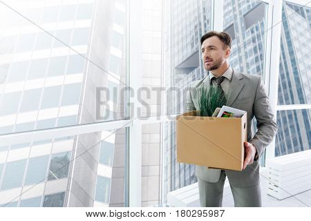 Ready to work. Pleasant handsome employee holding box with belongings and standing in the office