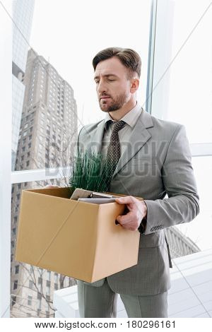 Time to find new job. Cheerless moody employee holding his belongings and feeling sad after being fired