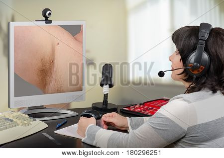 Telemedicine female dermatologist in headset looks at patient skin tags on monitor attentively. Virtual doctor sees underarm acrochordons either by online video chat or snapshot. Horizontal mid-shot on blurry indoors background poster