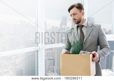 Black stripe of my life. Sad gloomy businessman standign near window with his belonngings and feeling gloomy because being fired