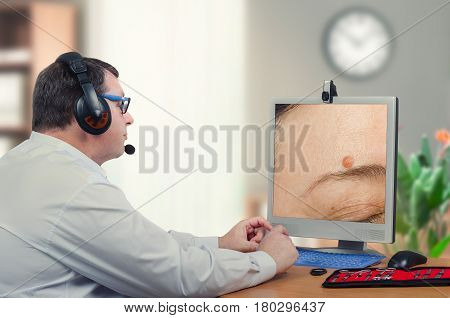 Telemedicine male dermatologist examines mole above womans eyebrow on computer monitor carefully. Virtual doctor looks at nevus on the right side of forehead either by online video chat or snapshot. Horizontal mid-shot on blurry indoors background