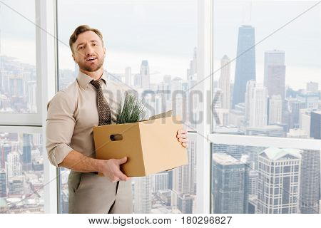 Career ladder. Positive office worker holding box with his belongings while getting ready to work in a new team