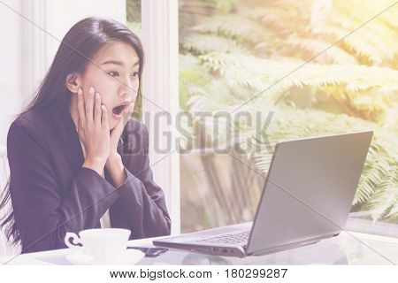 Beautiful young business woman working with a laptop, looking at screen with a gesture of rejoicing, shock, surprise emotion