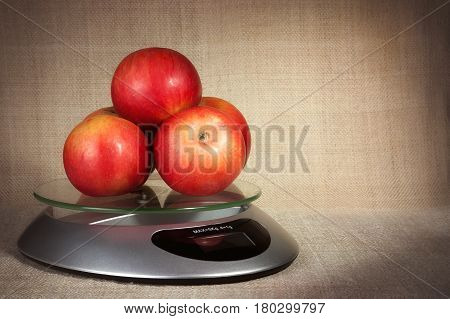 Red Apples On The Kitchen Scales On A Brown Background