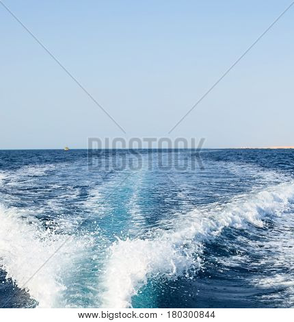 Background water wake surface behind fast moving motor boat
