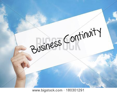 Man Hand Holding Paper With Text Business Continuity . Sign On White Paper. Isolated On Sky Backgrou