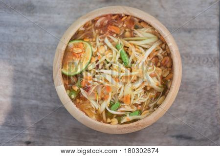 Green Papaya Salad (Som tum Thai) in wooden bowl on wood table Thai cuisine spicy delicious