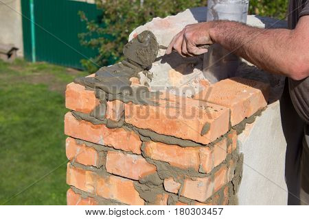 Builder mason building a chimney on the roof
