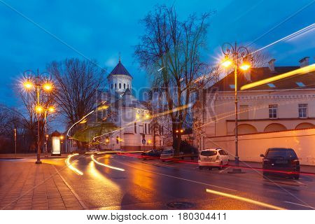 Picturesque Street and luminous track from the car at night in Old Town of Vilnius, Lithuania, Baltic states. Our Lady of the Assumption Orthodox Cathedral on the background.