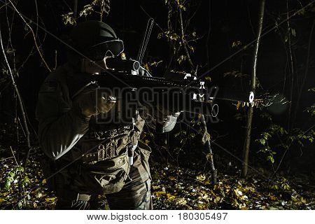 United states Marine Corps special operations command Marine Special Operator also known as Marsoc raider aiming weapons in the greenery at nighttime