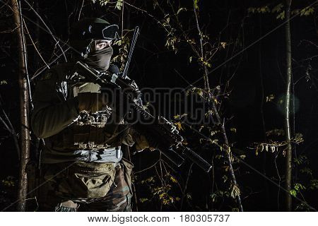 Marine Special Operator also known as Marsoc raider with weapons in greenery at nighttime turning looking away. Caucasian, profile view, half length