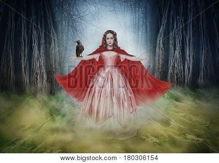 Beautiful woman in medieval dress and cloak with crow in fantasy forest