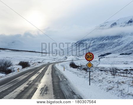 Winter Road With Mountain On The Side Of The Road Covered With Snow And A Road Sign Limiting Speed.