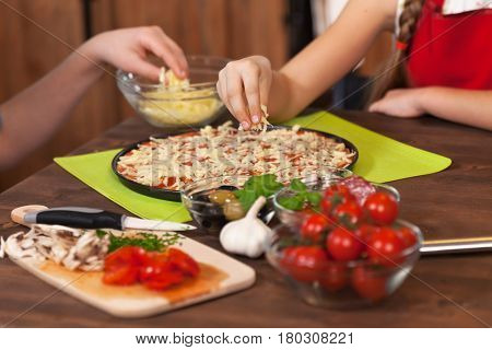 Kids making a pizza at home - preparing and placing ingredients on the dough, the shredded cheese, closeup