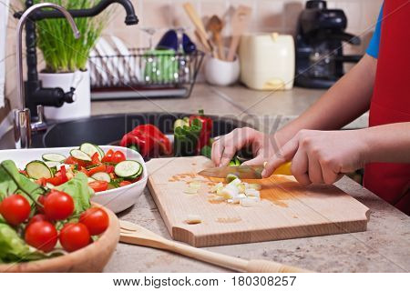 Child hands chopping vegetables on cutting board - making a fresh and healthy salad in the kitchen, closeup