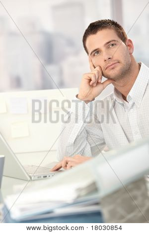 Daydreaming young man sitting at desk with lots of folders.?