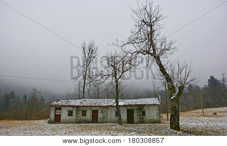 A dusting of snow on an old abandoned stone shack near Canebola in Friuli Venezia Giulia north east Italy poster