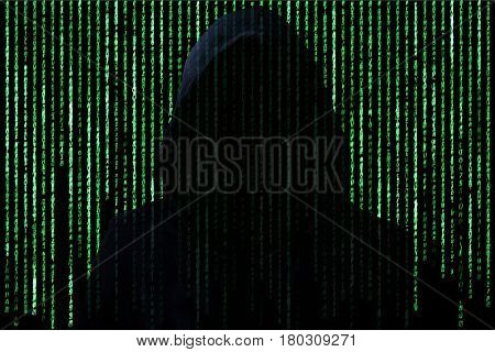 Hacker concept. Unrecognizable person in the hood break computer character codes.Green text on black background.
