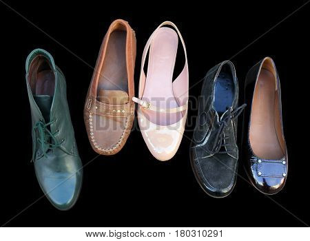 Closeup of five different casual vintage shoes isolated on black background.