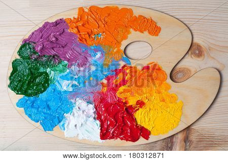 Artist's color palette with multi-colored oil paints