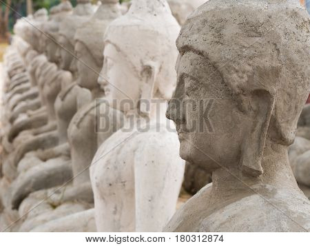 row of Buddha statue Made of cement in Thailand.
