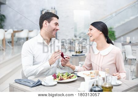Proposal in luxury restaurant. Lovely couple in cafe with stylish interior. Man with engagement ring