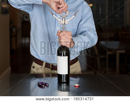 Senior caucasian man standing in kitchen opening bottle of red wine with a blank label for copy space