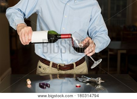 Senior caucasian man standing in kitchen pouring from bottle of red wine with a blank label for copy space
