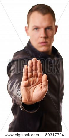 24 year old man in leather jacket - blured person - shows stop hand. concept of denial, refused