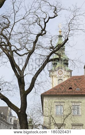 Tower of City Parish church building and tree at the main street of Graz the capital of Styria Austria