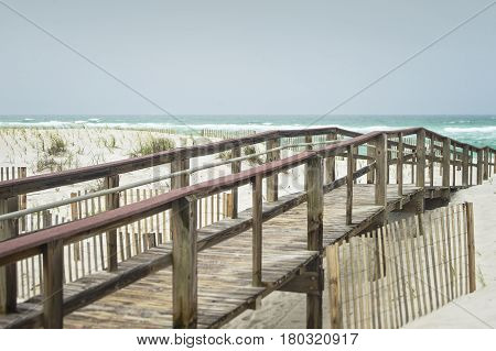 Beautiful beach on a stormy day in Florida on the boardwalk at the Gulf of Mexico with sand fences to prevent erosion.