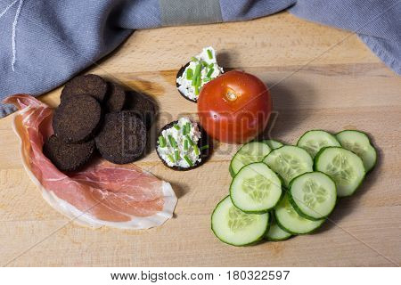 Pumpernickel with cream cheese on a wooden board with tomato cucumber discs and ham