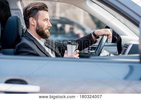 Handsome businessman driving a car with coffee to go in the city