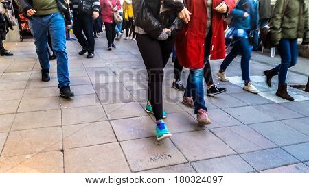 Crowd of people walking on the street. Detail of legs and shoes moving on sidewalk in city center.